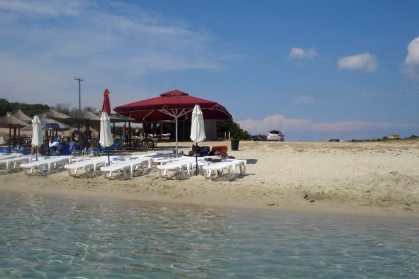 A part of Alikes beach on the island of Ammouliani including umbrellas, sunbeds, and the beach bar facilities.
