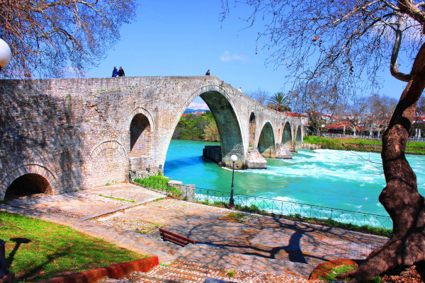 A picture showing the bridge of Arta with some people walking on it.