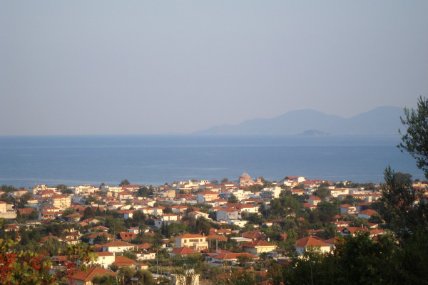 A panoramic photo depicting the houses of Asprovalta with the sea and the mountains as a background.
