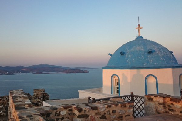 The blue-white dome of the Virgin Mary church on the hill of Astypalaia island and the great view in the background.