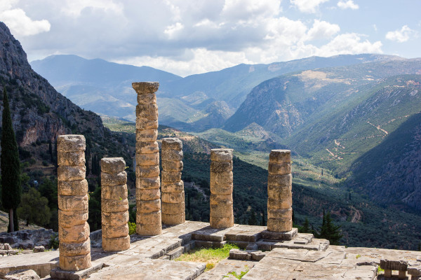 A part of the temple of Apollo in Ancient Delphi with the mountains of the area in the background.
