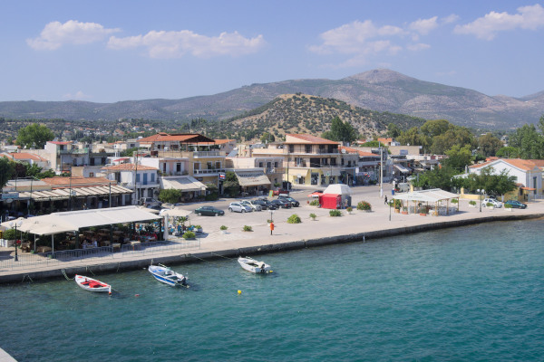 A panoramic picture of a part of the promenade of Eretria with three small boats anchored by the seafront.