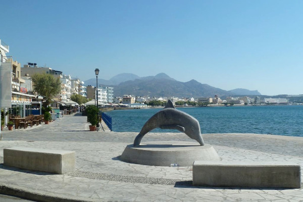 A dolphin statue and a part of the seaside promenade of Ierapetra.