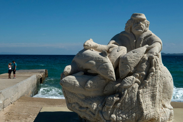 The statue of the fisherman located at the seafront of Ierissos having the deep blue sea and the blue sky as background.