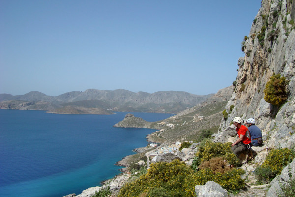 Two climbers by a steep cliff on the island of Kalymnos and the deep blue sea in the background.