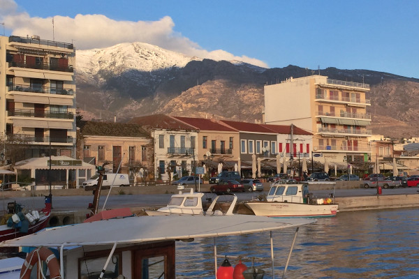 The promenade of Karystos with some small boats in the sea and the snowy peak of Ochi mountain in the background.
