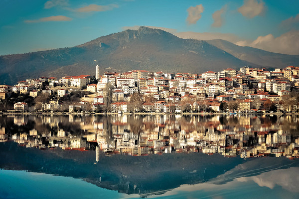 A part of the city of Kastoria and the mountain in the background reflecting at the calm waters of the lake.