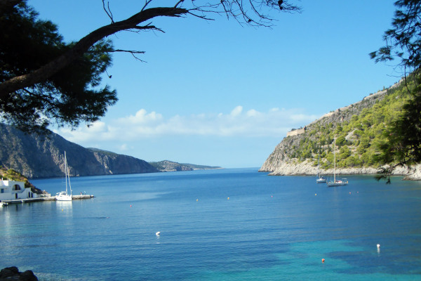 The blue sea and the light blue sky with the green coast at a bay of Kefalonia island.