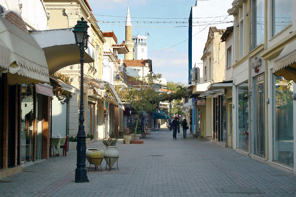 A central pedestrian street of Komotini with boutiques and shop displays on both sides.