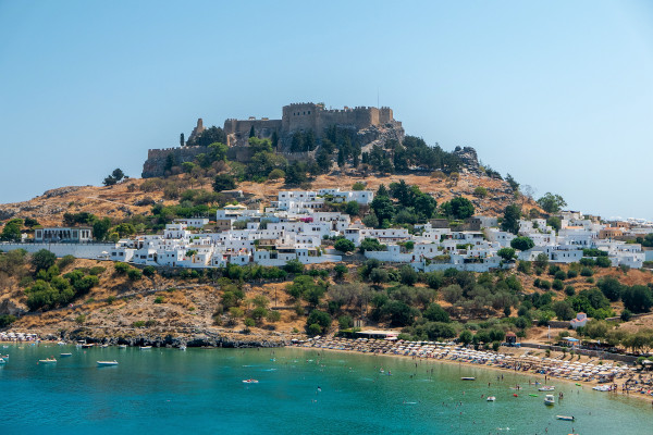 The fortification of the Acropolis of Lindos, the contemporary settlement, and the beach of the area.