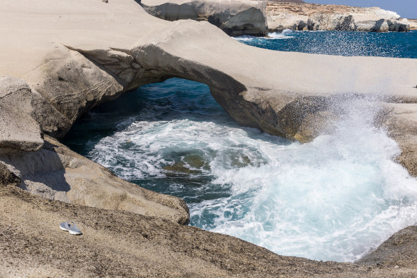 Natural arch and raw sea at the coast of the island of Milos, Greece.