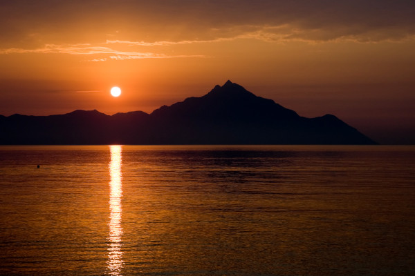The sunrise over the cliffs of Mount Athos while the sun is reflecting at the calm waters of the Aegean sea.