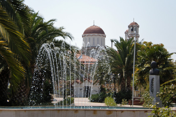The fountain of the square of Nea Poteidaia with the church of the town in the background.