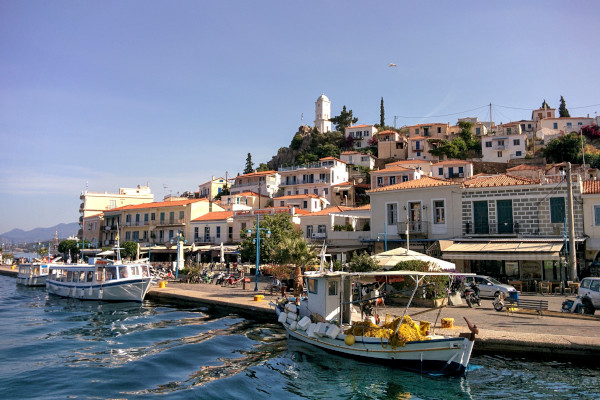 A photo taken from the sea shows a part of the settlement of Poros and some boats anchored by the seafront promenade.