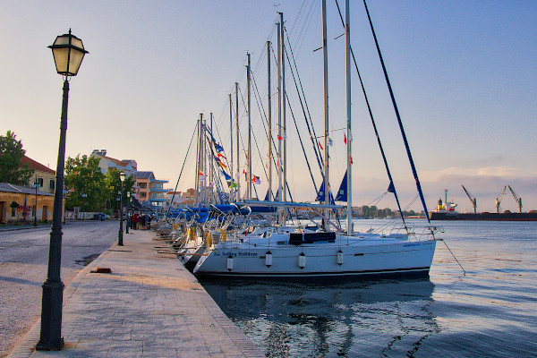 Numerous sailing vessels anchored in the quay by the seafront promenade of Preveza.