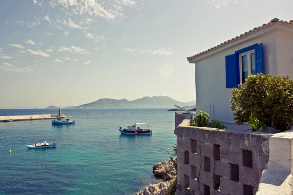 Small port with fishing boats in front of a traditional house built by the coast of Samos.