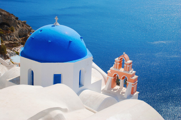 A blue-white dome and a belfry on Santorini island with the blue sea of the Aegean in the background.
