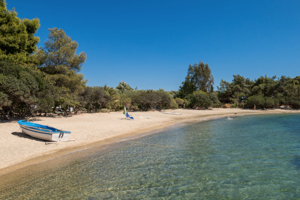 Clear waters, a small fishing boat on the sand, and dense vegetation very close to the beach of Galini, Neos Marmaras.
