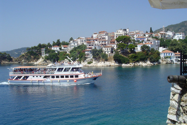 A boat full of people is approaching the port of Skiathos.