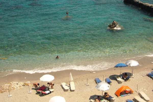 An overview of a sandy beach in Skopelos with the sun-umbrellas reaching almost the water.