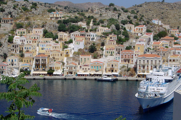 A big ship in the port and a part of the settlement of Symi, Greece.