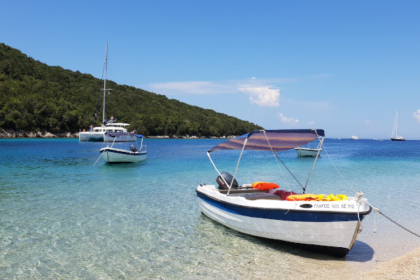 Small boats and a catamaran anchored by a sandy beach of turquoise waters.