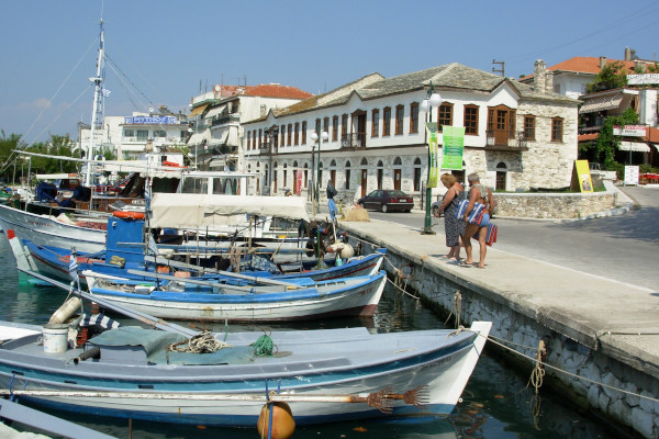 Traditional buildings of the seaside promenade of the central port of Thasos (Limenas) and small boats on the sea.
