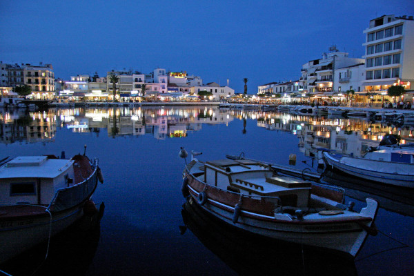 Picture taken from one shore of Agios Nikolaos Lake, includes some anchored boats and the nearby shops and restaurants.