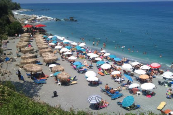 A photo showing many people under umbrellas and others who are sunbathing at the Agiokampos Beach of Agia (Melivoia).