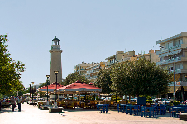 Cafeteria seating places at the square of Alexandroupolis with the lighthouse of the city in the background.