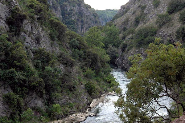 A close-up of the Aggitis gorge including the river flow, the steep cliffs, and the lush area vegetation.