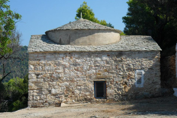 The old stone-built church of Saints Anargyroi in Alonnisos in dense forest.