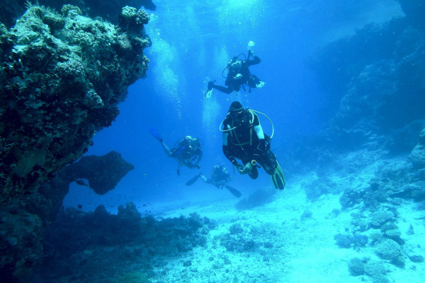 Four scuba divers on their way to the shipwreck, surrounded by huge rocks.