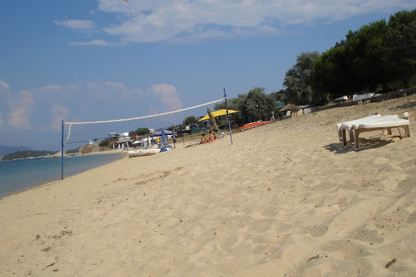 A photo of the Agios Georgios Beach on Ammouliani showing a beach volley court a sunbed and some facilities.