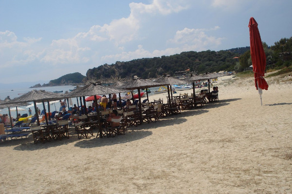 The umbrellas and the sunbeds of a beach bar at the Alykes beach of Ammouliani.