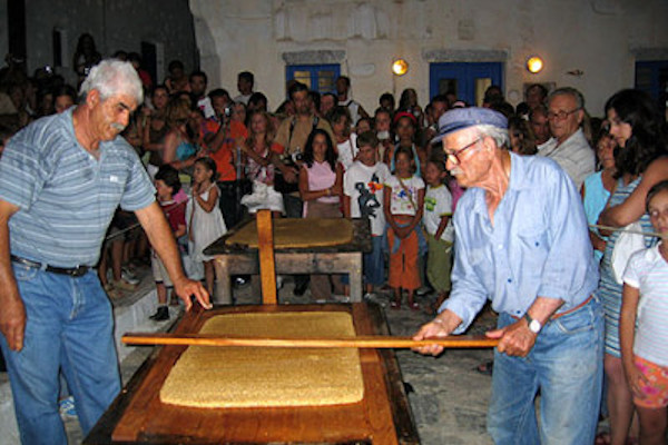 Two older men during the preparation of pasteli and plenty of people in the audience in the background.