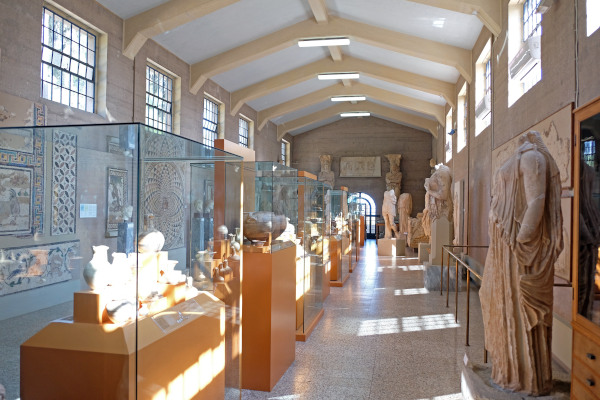 A photo of the corridor of the Archaeological Museum of Ancient Corinth with statues and exhibits.