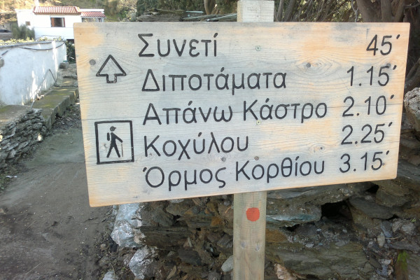 A wooden sign showing the distance in minutes between the hiking destinations on the island of Andros.