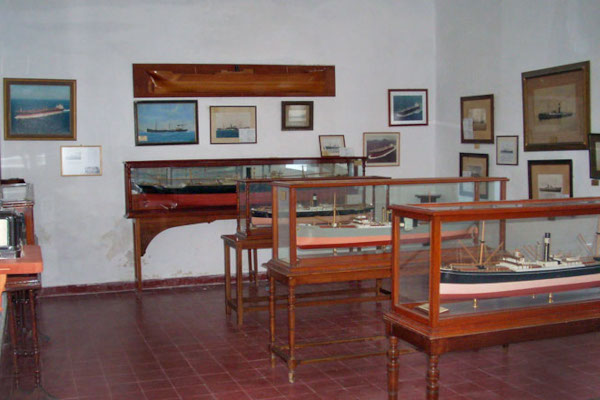 A picture of one of the rooms of the Andros Maritime Museum with displays and other exhibits hanging on the wall.