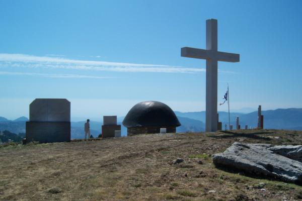 A big cross, a Greek flag and the memorial at the hill of Annítsa.