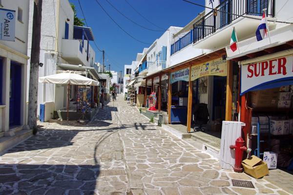 A central narrow cobblestone street on the island of Antiparos with shops on both sides.