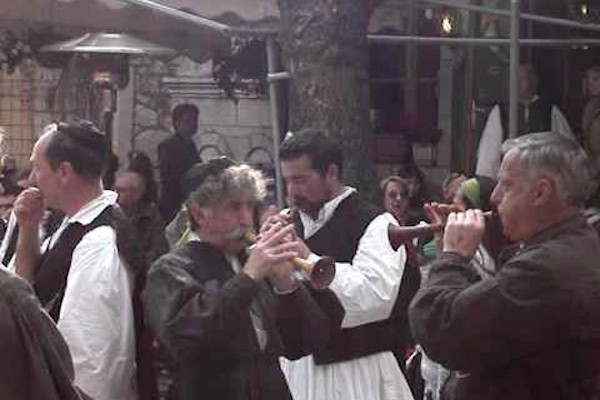 People playing musical instruments and other participants of the Arachova-Saint George celebration.