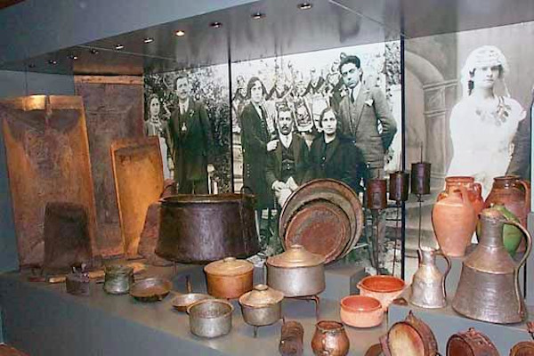 A display with utensils and everyday tools as well as some photographs showing the life of people in old Arnaia.