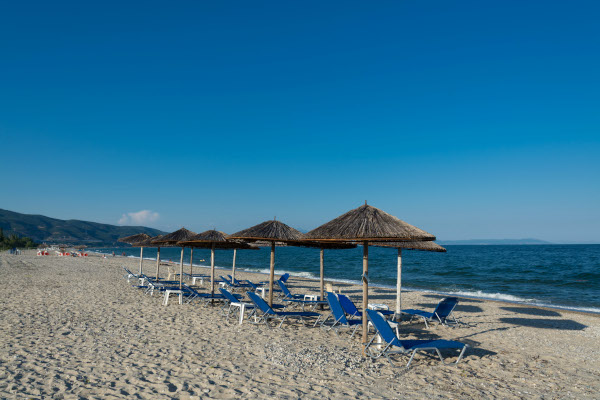 Umbrellas and sunbeds lying on the beach of Asprovalta.
