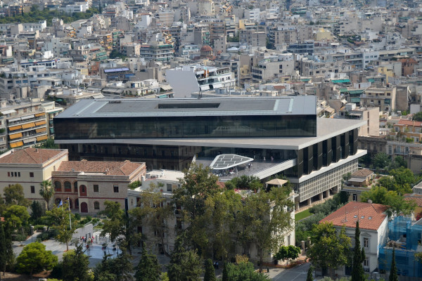 A view of the exterior of the Acropolis museum in Athens among hundreds of modern buildings.