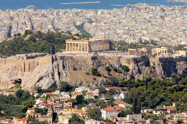 An aerial view of the Acropolis Hill and Plaka in the midst of a densely populated modern Athens.