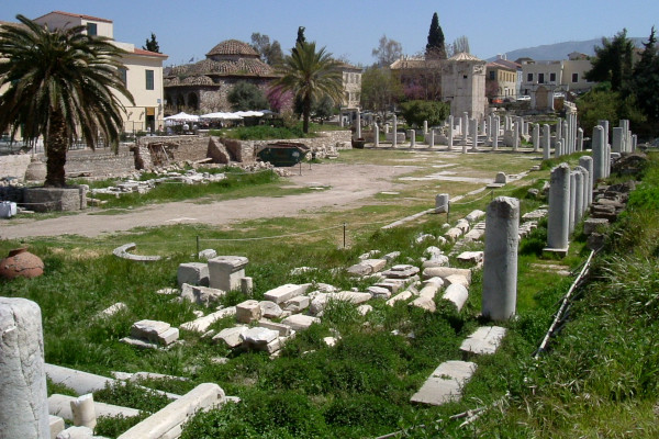 A picture showing white columns and other remains of the Roman Agora of Athens spread around on grassy grounds.