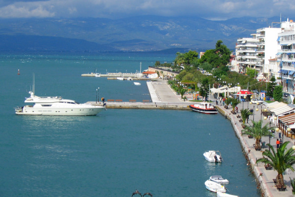 An overview of the seafront promenade of Chalkida with a yacht and some smaller boats anchored by the coast.