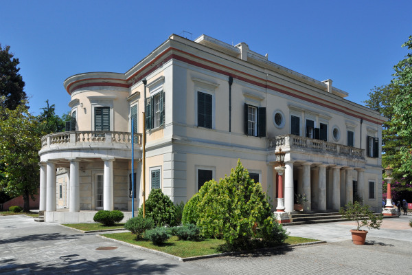 The exterior of the royal villa of Mon Repos shows a neo-classic white palace with Greek columns.