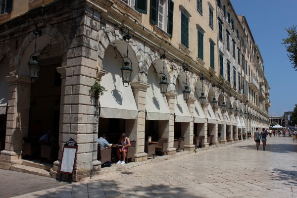 A picture of the Liston pedestrian street in Corfu with people enjoying their coffee at the local cafeterias.